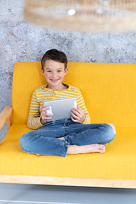 7 year old boy playing with tablet on yellow couch in front of concrete wall - p300m2170371 von Epiximages