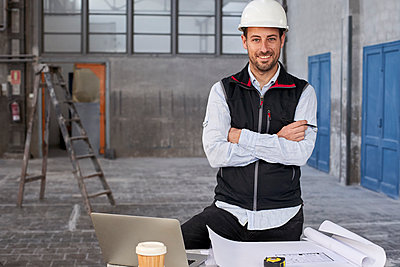 Confident male architect with arms crossed standing at table in building - p300m2244183 by Veam