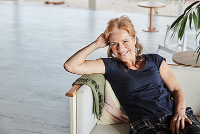 Happy mature woman with hand in hair sitting on sofa at home - p300m2265223 by Jo Kirchherr