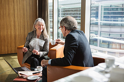 Businessman and businesswoman in coffee area in office, London, UK - p429m1448130 by Nancy Honey