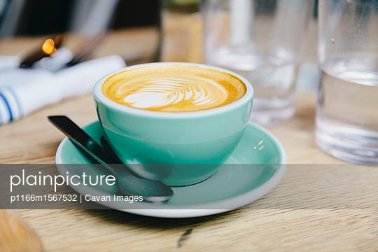 plainpicture - plainpicture p1166m1567532 - Close-up of frothy drink se... - plainpicture/Cavan Images
