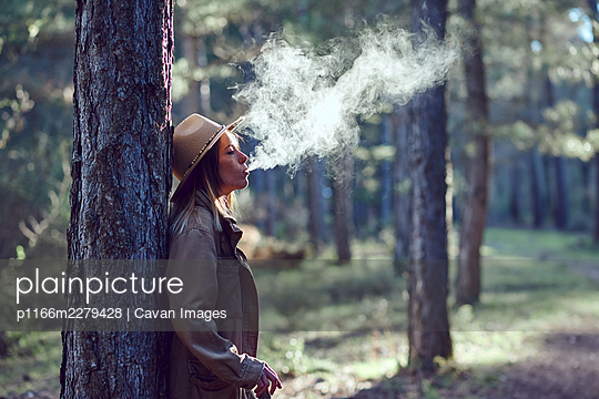 Woman on the mountain. She is in a forest with pine trees. - p1166m2279428 by Cavan Images