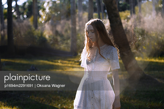 Back view of a red-haired young woman in a delicate dress walking in the sunny forest  - p1694m2291691 by Oksana Wagner