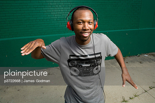 African-American man wearing headphones, dancing - p3722668 by James Godman