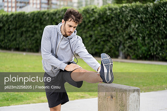 Young man exercising in public park - p623m2258205 by Frederic Cirou