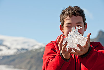 teenage boy holding up ice from glacier lagoon in Iceland - p1166m2279420 by Cavan Images