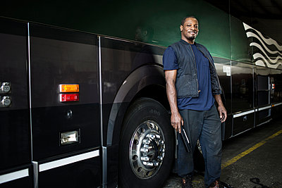 Portrait of mechanic standing by bus in repair shop - p1166m995297f by Cavan Images