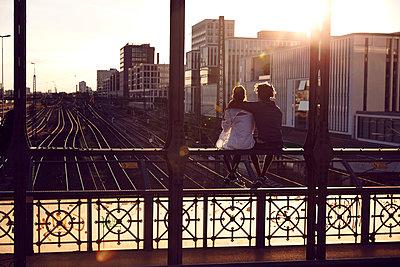 Germany, Munich, Young couple sitting on bridge, enjoying sunset - p300m1494758 by Sullivan