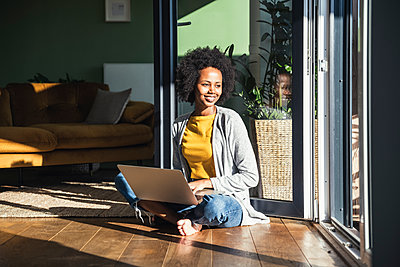 Smiling young woman with laptop sitting in sunlight at home - p300m2300509 by Uwe Umstätter