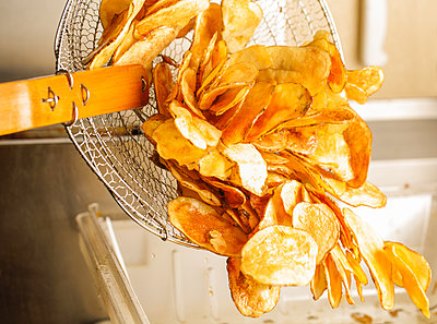 Feshly-Fried Potato Chips Being Poured Out Of A Fryer Basket - p343m1223893 by Clay McLachlan