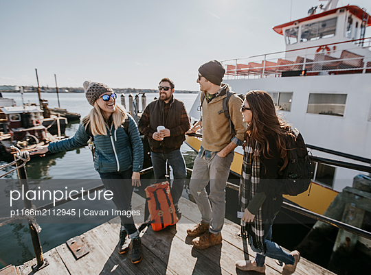 Four young adult friends wait on the waterfront in Portland, Maine - p1166m2112945 by Cavan Images