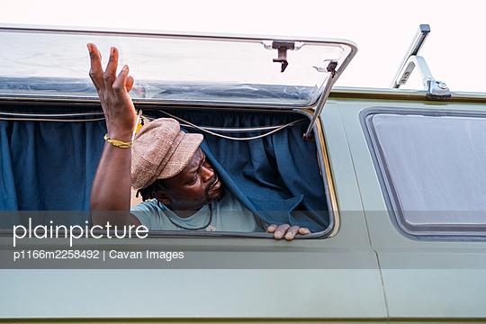 black african american man inside his camper van at the window - p1166m2258492 by Cavan Images