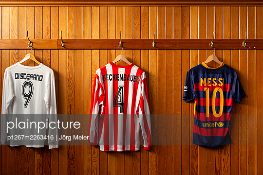 Various football shirts on the coat hook - p1267m2263416 by Jörg Meier