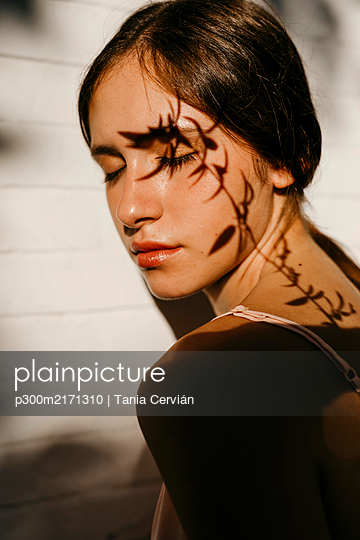 Portrait of teenage girl with shadow of leaves on her face - p300m2171310 by Tania Cervián