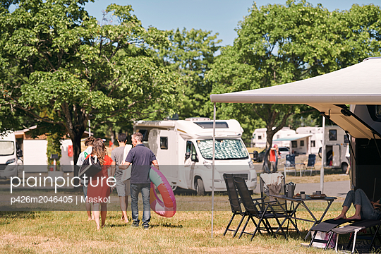 Rear view of family with inflatable rings walking by camper vans at trailer park - p426m2046405 by Maskot