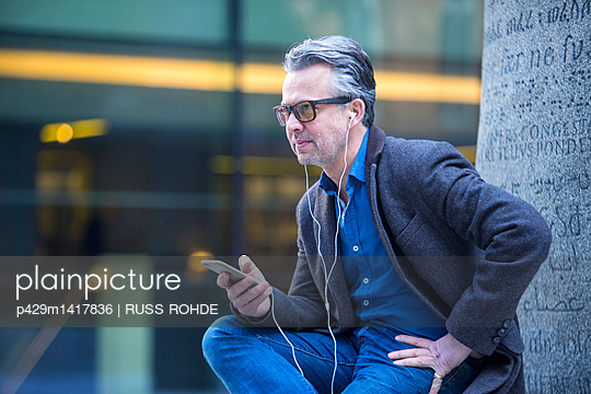 Man with smartphone and earbuds sitting outdoors - p429m1417836 by RUSS ROHDE