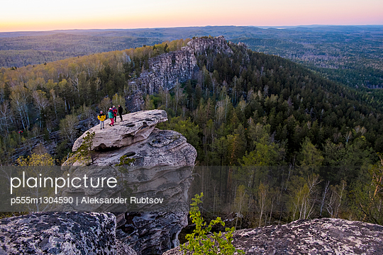 Caucasian friends standing on mountain rock admiring scenic view - p555m1304590 by Aleksander Rubtsov