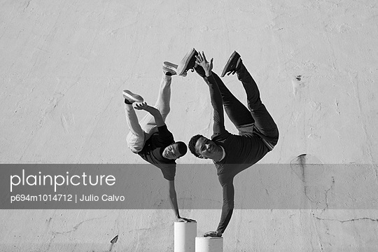 Two Athletic Teen Boys Balancing on Posts with One Hand