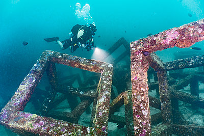 diver exploring an artificial reef structure at Raja Yai  / Phuket - p1166m2190823 by Cavan Images