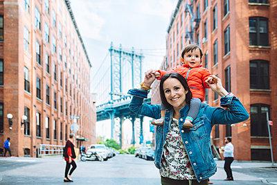 USA, New York, New York City, Mother and baby in Brooklyn with Manhattan Bridge in the background - p300m1587361 von Gemma Ferrando