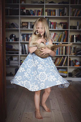 Blond little girl dancing with her Burmese cat at home - p300m2155951 by Ekaterina Yakunina