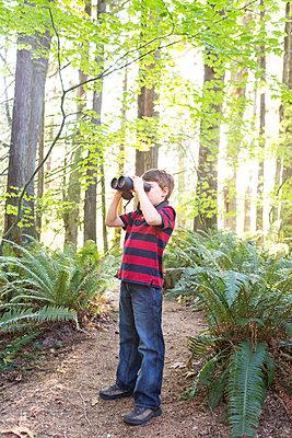 Caucasian boy using binoculars in forest - p555m1479544 by Adam Crowley