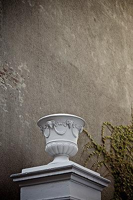 Amphore auf einem Sockel vor einer verwitterten Hauswand - p586m973076 von Kniel Synnatzschke