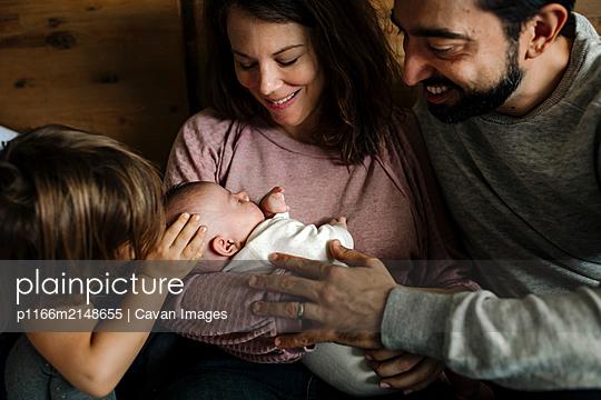 Family love embracing newborn baby - p1166m2148655 by Cavan Images