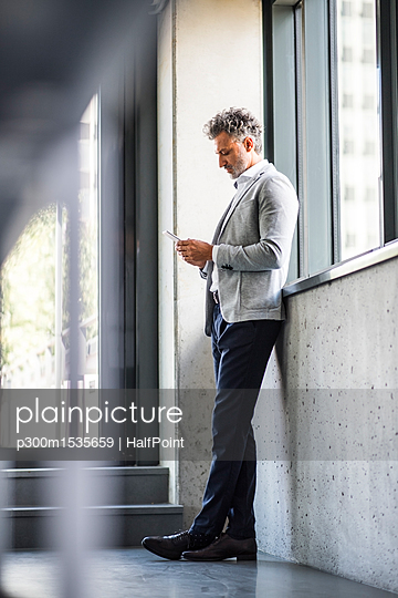 Mature businessman standing at the window holding cell phone - p300m1535659 by HalfPoint