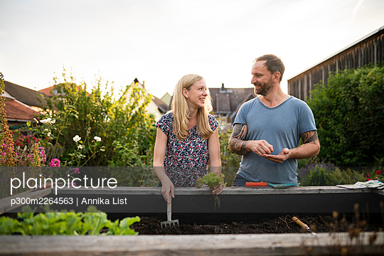 Smiling couple doing gardening while discussing at garden - p300m2264563 by Annika List