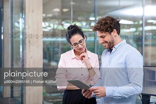 Young male entrepreneur with digital tablet discussing with female colleague against glass wall at office - p300m2265165 by Florian Küttler