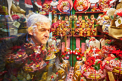 Man looks in a shop window with sweets - p1312m2082191 by Axel Killian