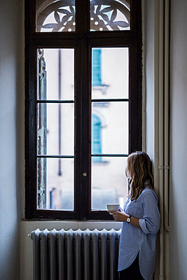 Woman with cup of coffee at home looking out of window - p300m1535346 by Giorgio Fochesato