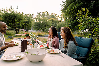 Smiling woman and daughter talking to father while sitting by dining table in yard - p426m2227859 by Maskot