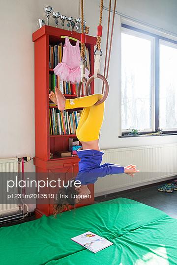 Mädchen hängt kopfüber und liest - p1231m2013519 von Iris Loonen