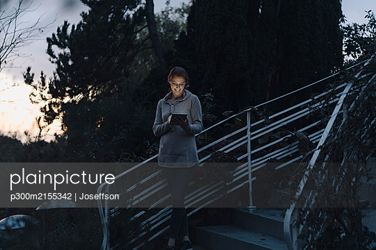 Woman using digital tablet in twilight, standing on stairs in garden - p300m2155342 by Joseffson