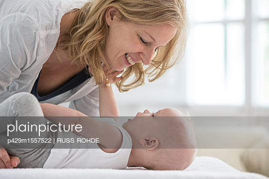 Baby boy lying on bed face to face with mother - p429m1557522 by RUSS ROHDE