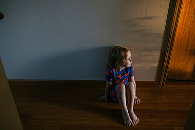 Little Girl Sitting On the Floor as the Sun Sets - p1238m1042071 by Amanda Voelker