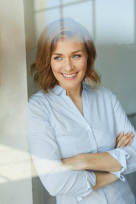 Portrait of smiling businesswoman  looking out of window - p300m2024000 von Philipp Nemenz