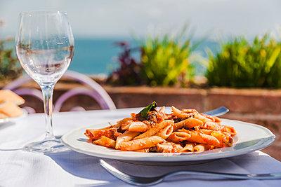Italy, Atrani, plate of Penne Rigate with tomato sauce and tuna - p300m2041841 von Flavia Morlachetti