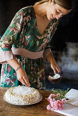 Smiling young woman garnishing home-baked cake - p300m2059918 von Alberto Bogo