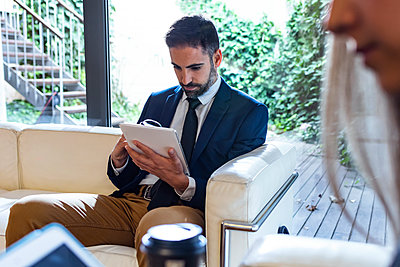 Businessman using tablet in lounge - p300m2160669 by Josep Suria