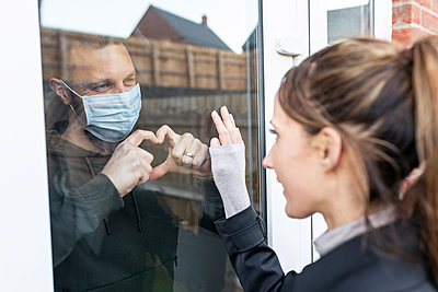 Boyfriend show heart shape gesture to girlfriend through window glass while quarantined at home - p300m2241417 by William Perugini