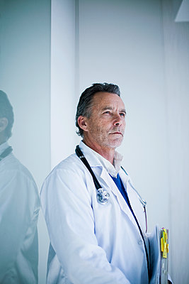 Male senior doctor with documents standing in hospital - p300m2281413 by LOUIS CHRISTIAN