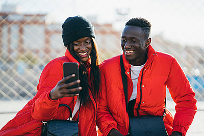 Happy couple in red jackets using smart phone outdoors - p300m2282448 by Manu Padilla Photo