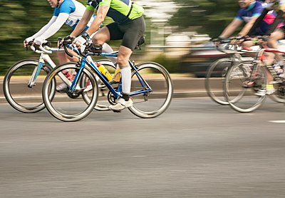 Four racing cyclists speeding on urban road in racing cycle race - p429m1118422f by Seb Oliver