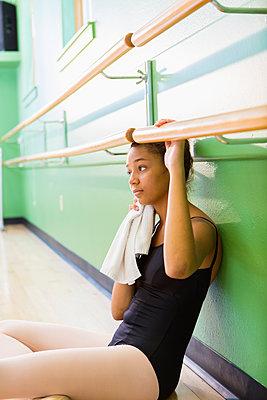 Mixed race ballerina sitting below barre - p555m1463772 by Marc Romanelli
