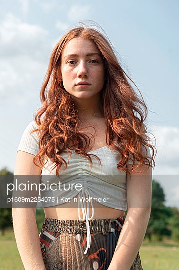 Red-haired young woman against  blue sky, portrait - p1609m2254075 by Katrin Wolfmeier