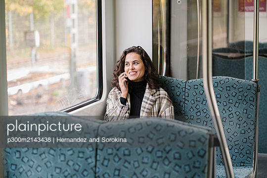 Smiling young woman on the phone on a subway - p300m2143438 by Hernandez and Sorokina