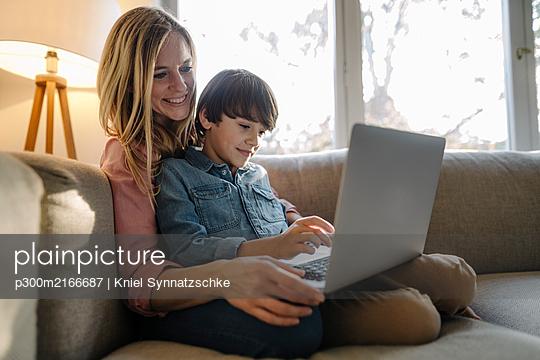 Mother and son sitting on couch, using laptop - p300m2166687 von Kniel Synnatzschke